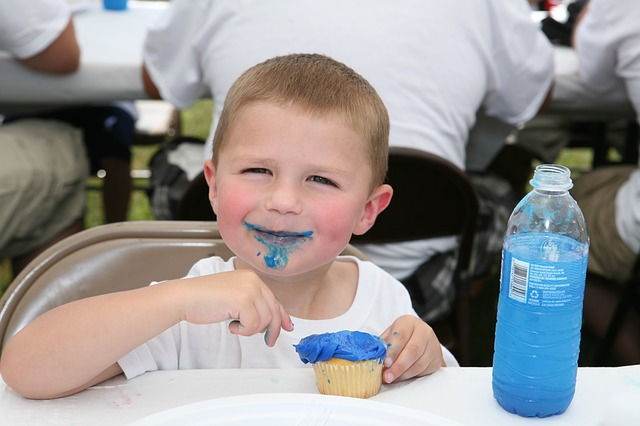 Young Boy Eating Cupcake w/ Blue Icing